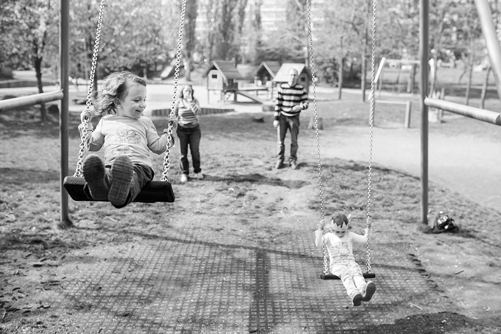 family on playground swings